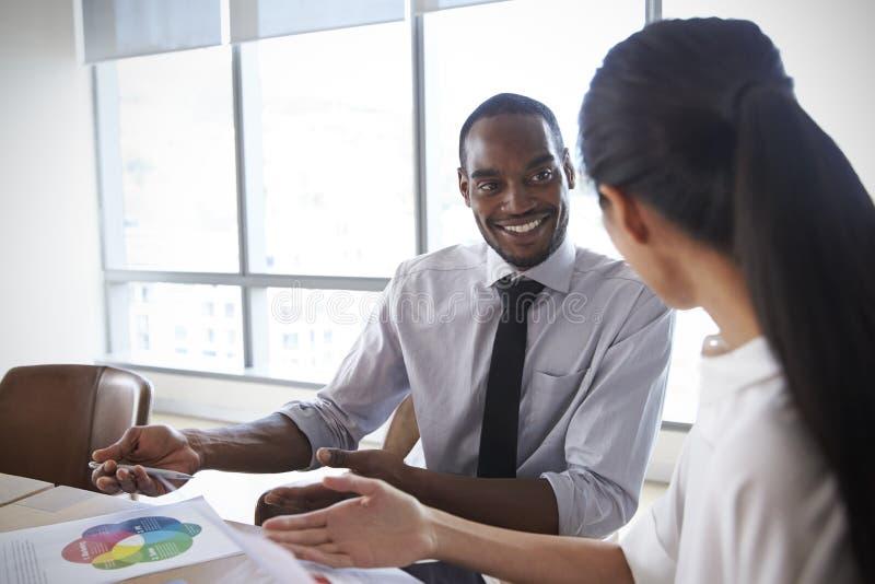 Businesspeople som tillsammans arbetar på bärbara datorn i styrelse royaltyfri bild