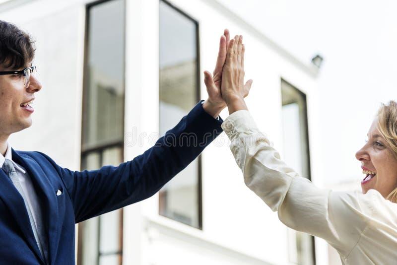 Businesspeople som tillsammans ger höga fem royaltyfri bild