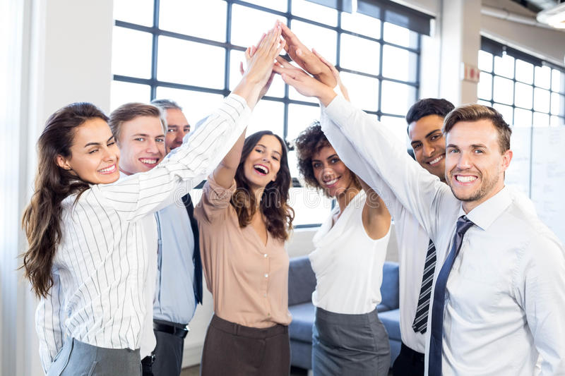 Businesspeople stacking hands in office stock images