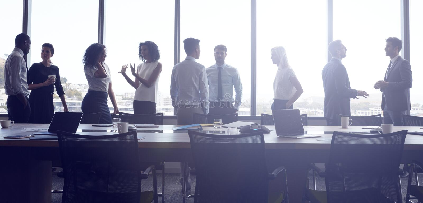 Businesspeople Stand And Chat Before Meeting In Boardroom stock images