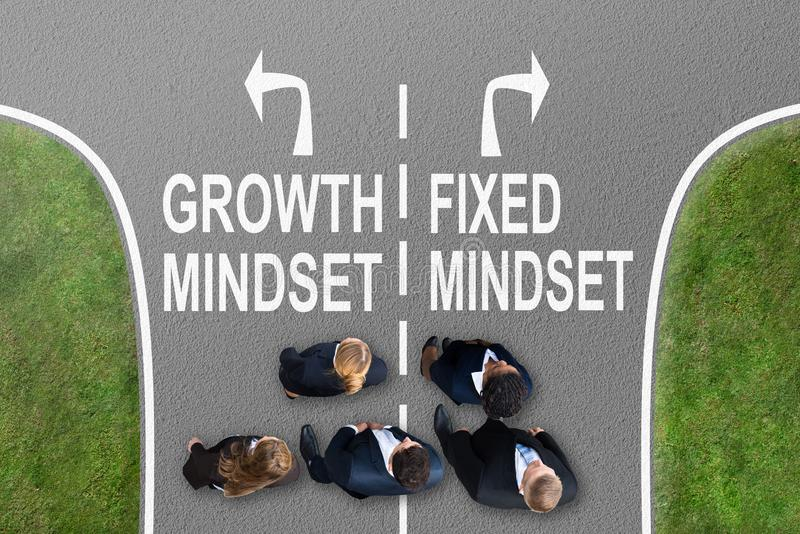 Businesspeople Near Signs Growth Mindset And Fixed Mindset. Businesspeople Standing On Road With Arrow Sign Showing Growth Mindset And Fixed Mindset Direction royalty free stock image