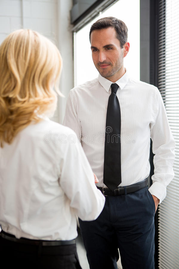 Businesspeople standing up and shaking hands. Half length portrait of two businesspeople standing up and shaking hands royalty free stock photography