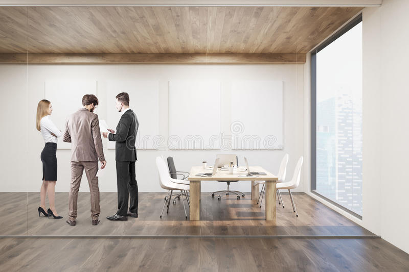 Businesspeople talking in conference room with four posters royalty free stock image
