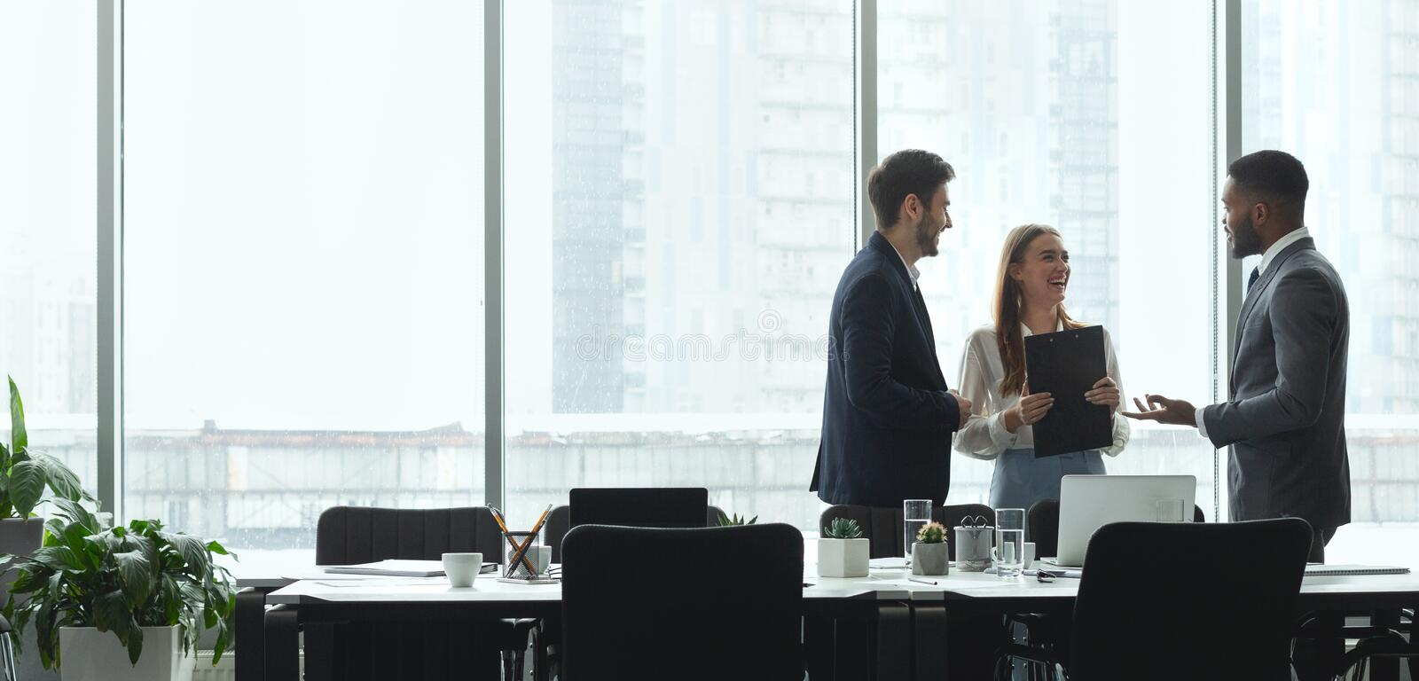 Businesspeople talking in office, standing against window. By table, panorama, copy space royalty free stock image