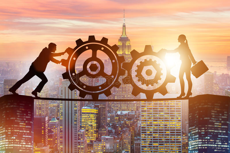 The businesspeople in teamwork example with cogwheels. Businesspeople in teamwork example with cogwheels stock photos