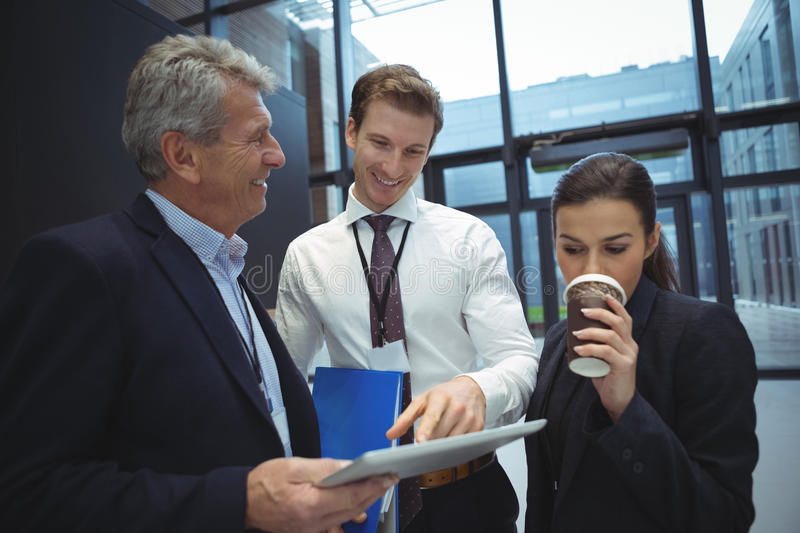 Businesspeople using digital tablet while having coffee royalty free stock images