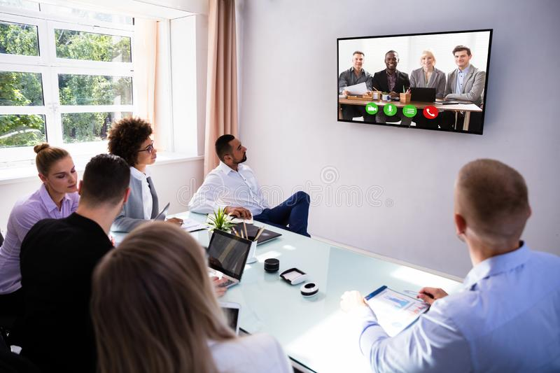 Businesspeople Video Conferencing In Boardroom. Group Of Skillful Businesspeople Video Conferencing In Boardroom stock images