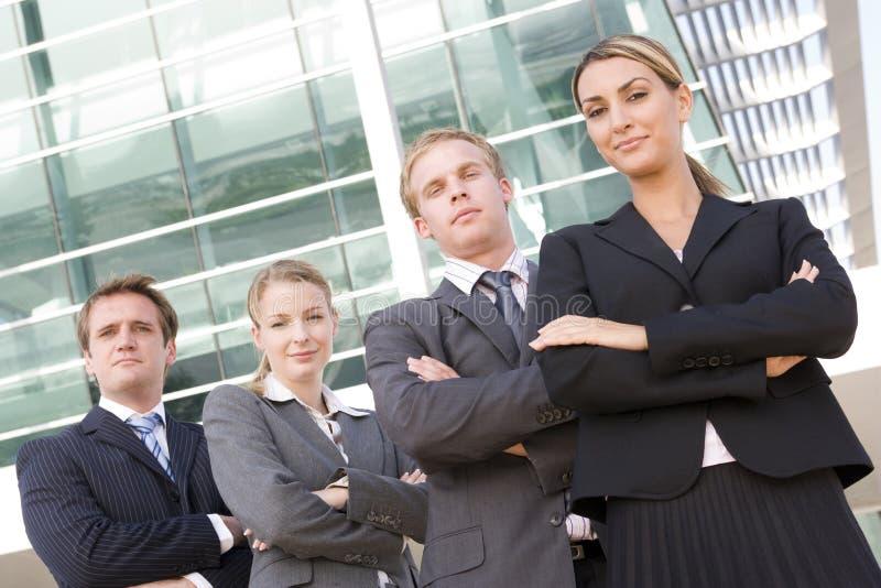 Businesspeople vier die in openlucht bevindt zich glimlachend stock afbeelding