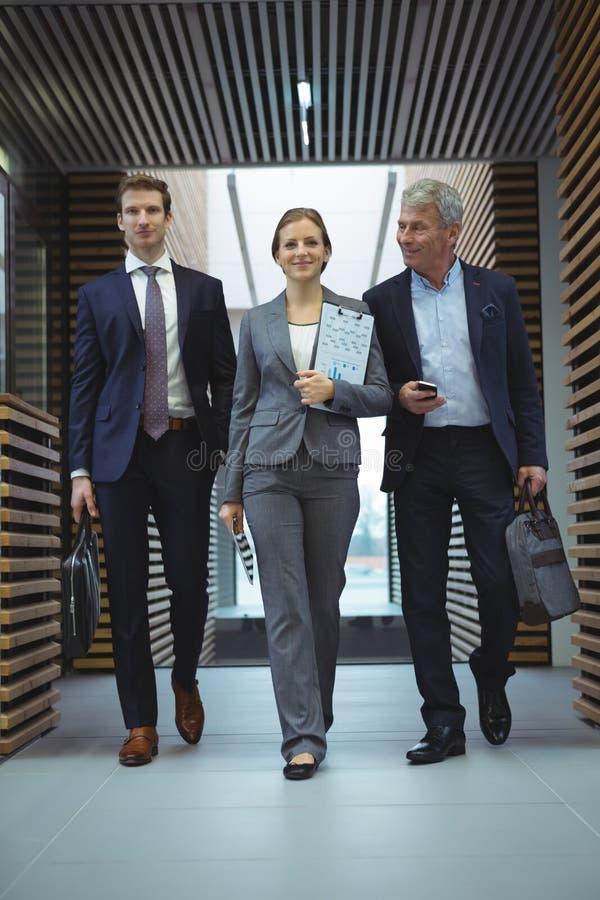 Businesspeople walking in corridor stock photos