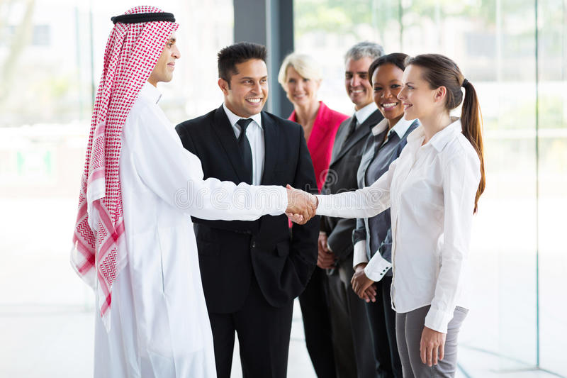 Businesspeople welcoming Islamic businessman stock photography