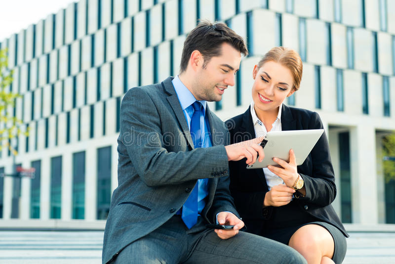 Businesspeople working outdoor with tablet computer stock photo