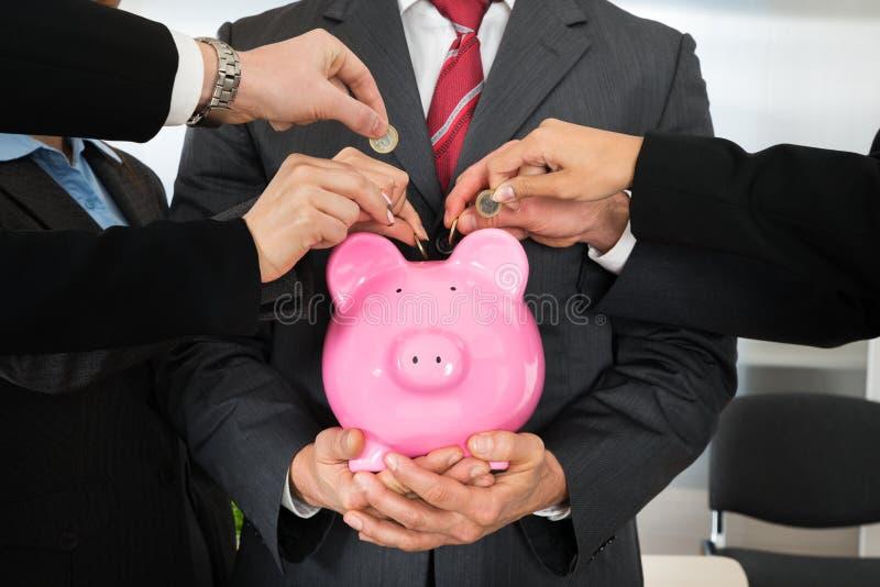 Businesspeoplehänder med mynt och piggybank arkivfoto