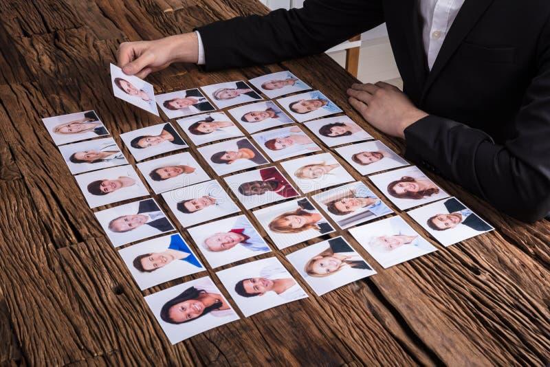 Businessperson που επιλέγει τη φωτογραφία του υποψηφίου στοκ εικόνες