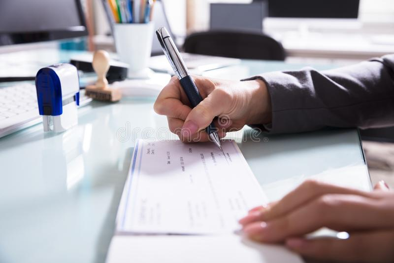 Businessperson που υπογράφει την επιταγή στην αρχή στοκ φωτογραφίες