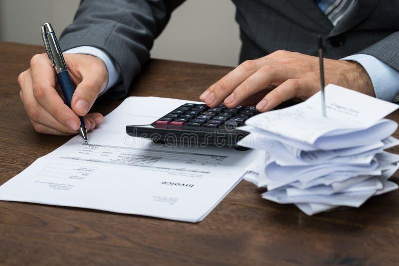 Businessperson που υπολογίζει τις οικονομικές δαπάνες στοκ εικόνα