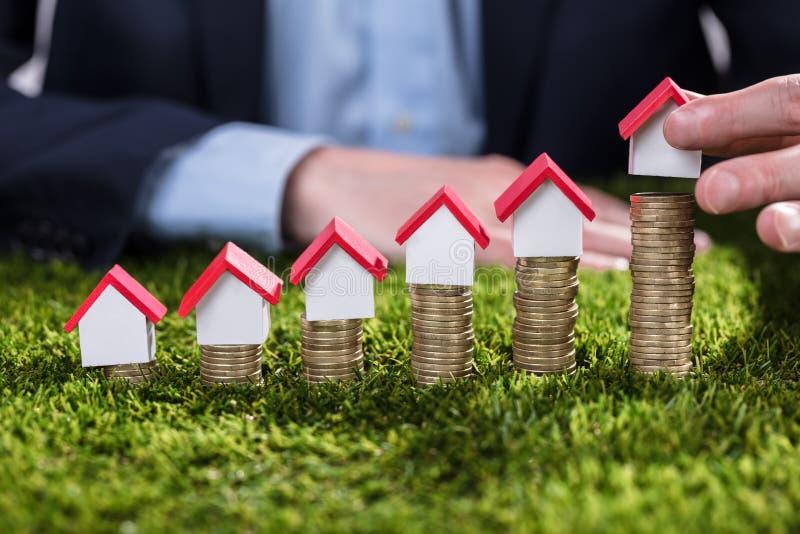 Businessperson Arranging House Model över staplade mynt fotografering för bildbyråer