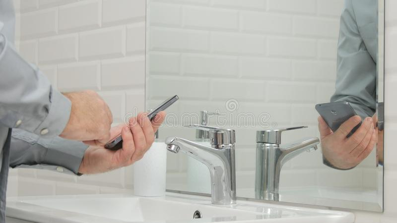 Businessperson in Badkamers die Zijn Mobiele Telefoontekst gebruiken vóór het Wassen van Handen stock foto