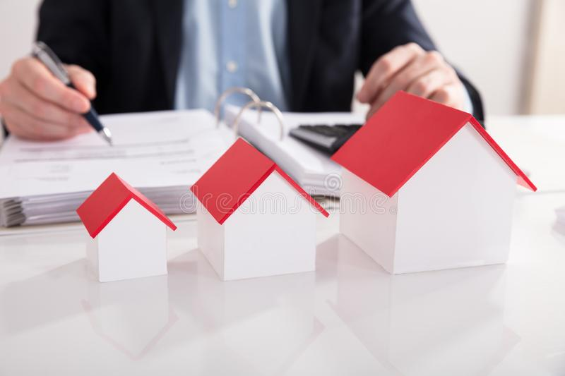 Different Size Of House Model In A Row. Businessperson Calculating Bill Behind Different Size Of House Model In A Row stock photography