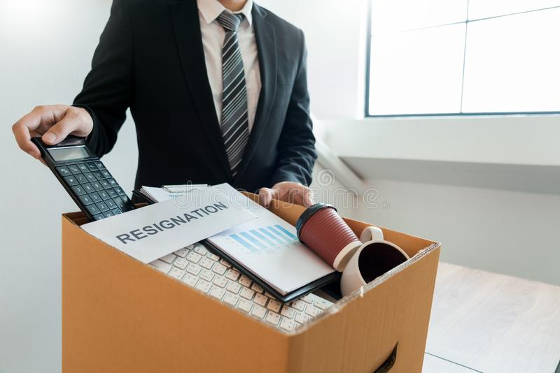 Businessperson carrying packing personal company on brown cardboard Box and resignation letters for quit or change of job leaving royalty free stock photo