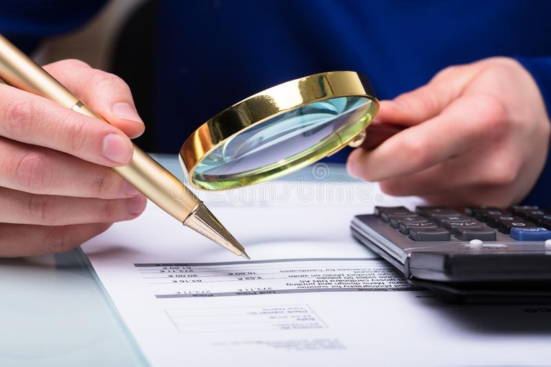 Businessperson Checking Bill Through Magnifying Glass arkivfoto