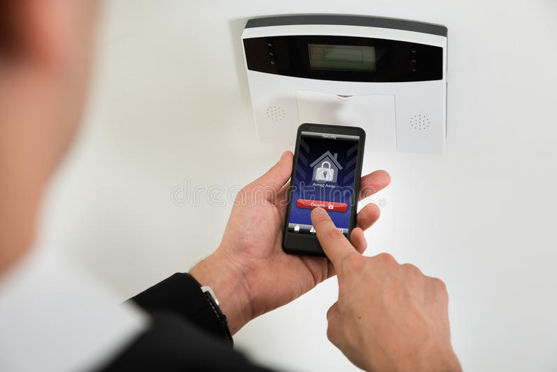 Businessperson Disarming Security System With Mobile Phone. Close-up Of Businessperson Hands Disarming Security System Of Door With Mobile Phone royalty free stock photography