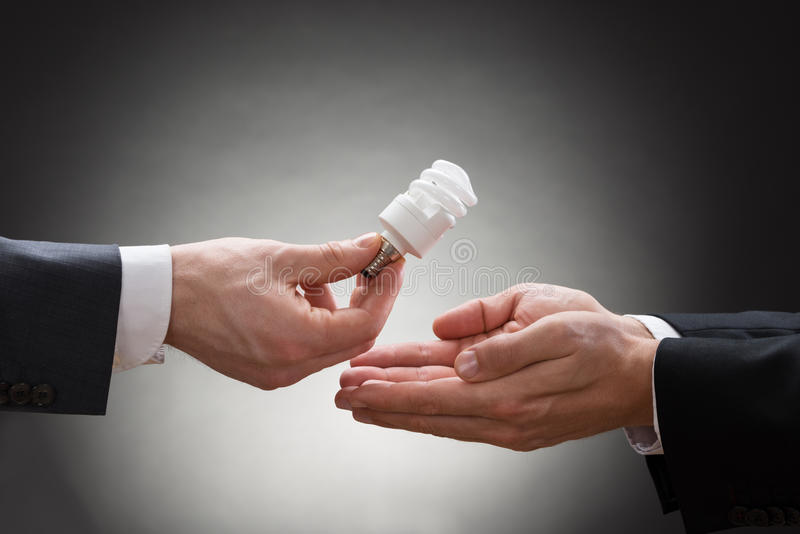 Businessperson hand offering light bulb to other businessperson stock photos
