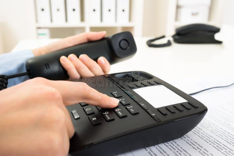 Businessperson het draaien aantal op telefoontoetsenbord royalty-vrije stock afbeelding