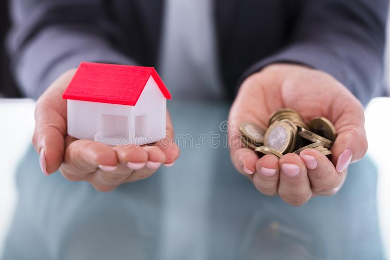 Businessperson Holding Coins And House Model. Close-up Of A Businessperson`s Hand Holding Coins And House Model royalty free stock photography
