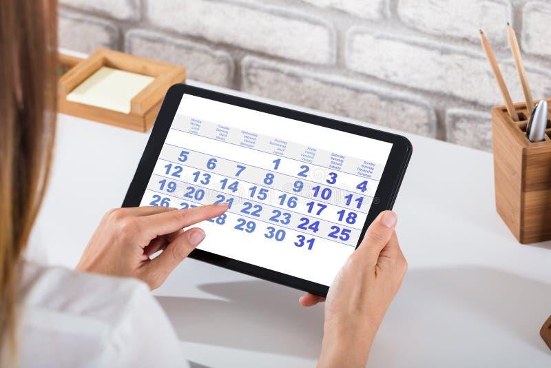 Businessperson Holding Digital Tablet med kalendern på skärmen royaltyfria foton
