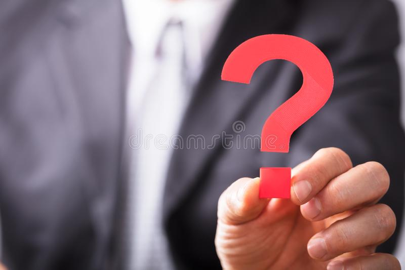 Businessperson Holding Question Mark Sign. Close-up Of A Businessperson`s Hand Holding Red Question Mark Sign royalty free stock photo