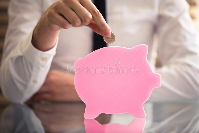 Businessperson Inserting Coin In plana Piggybank arkivbilder