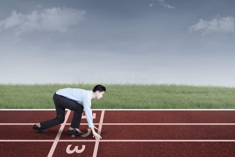 Businessperson klaar te rennen en te concurreren stock foto