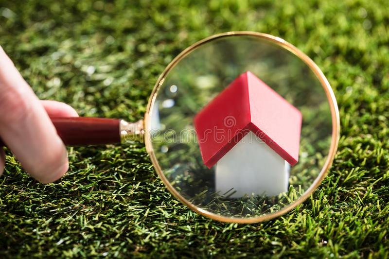Businessperson Looking At House Modelthrough magnifying glass royalty-vrije stock afbeelding