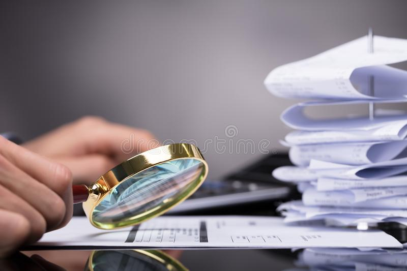Businessperson Looking At Invoice till och med förstoringsglaset arkivbilder
