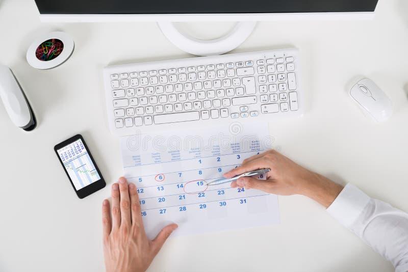 Businessperson Marking Important Date på kalender royaltyfri bild