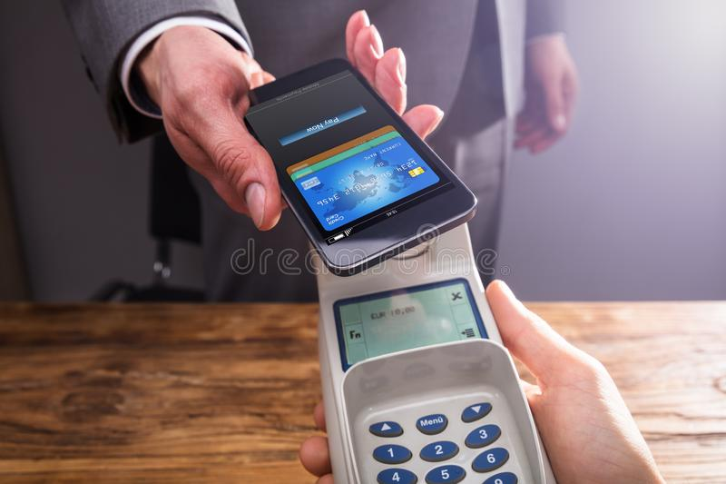 Businessperson Paying With Smartphone som använder NFC-teknologi arkivbilder