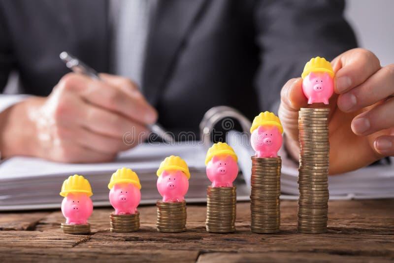 Businessperson Placing Piggybank On die Gestapelde Muntstukken verhogen stock afbeeldingen