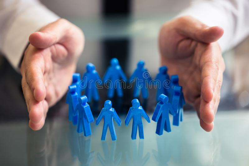 Businessperson Protecting Blue Human Figures Forming Circle stock photo