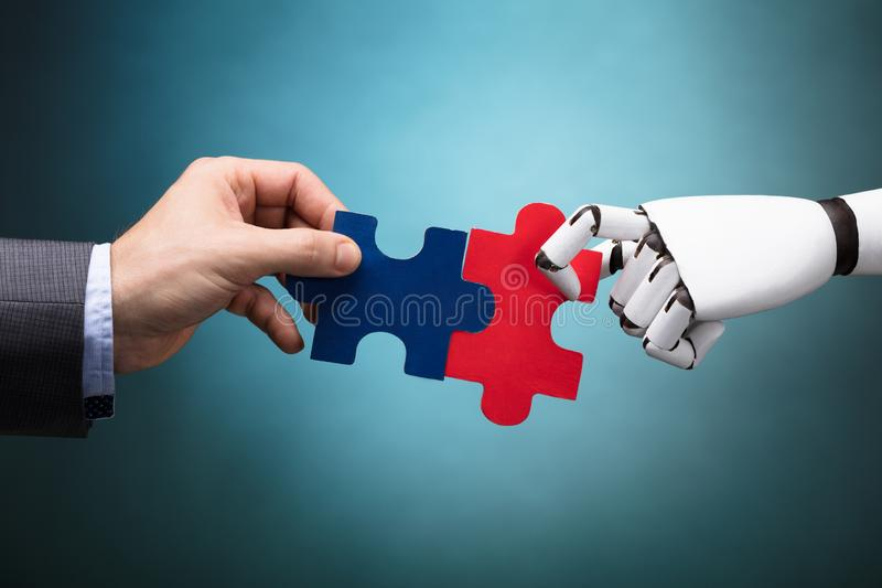 Businessperson And Robot Holding Jigsaw Puzzle. On Turquoise Background stock image