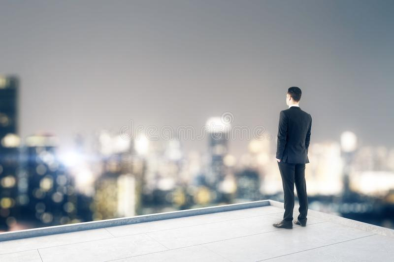 Businessperson on rooftop. Businessperson looking into the distance on rooftop with blurry night city view. Copy space. Success, vision and future concept stock images
