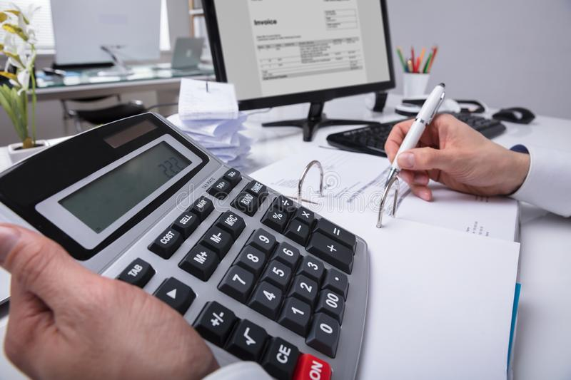 Businessperson`s Hand Calculating Bill royalty free stock image