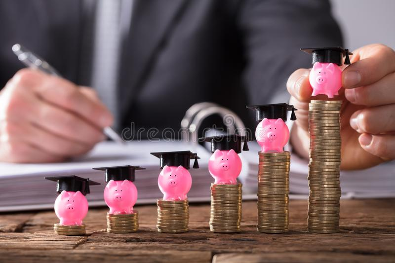 Businessperson Placing Piggybank With Graduation Cap. Businessperson`s Hand Placing Piggybank With Graduation Cap On Increasing Stacked Coins Over Wooden Desk stock photo