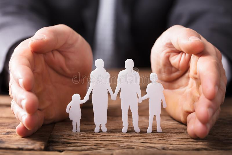 Businessperson`s Hand Protecting Family Figures. Close-up Of A Businessperson`s Hand Protecting Family Figures On Wooden Desk royalty free stock photos