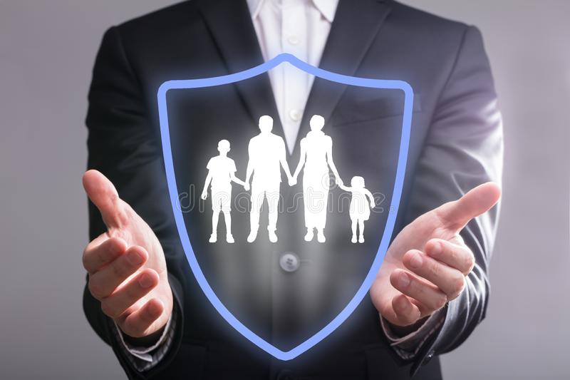 Businessperson`s Hand With Shield Protecting Family stock image