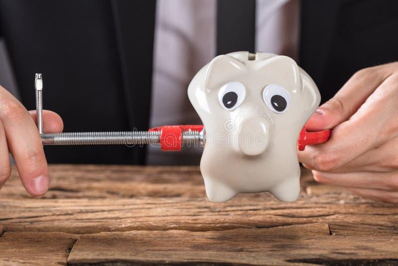 Businessperson Squeezing Piggy Bank i klämmahjälpmedel på skrivbordet royaltyfria bilder