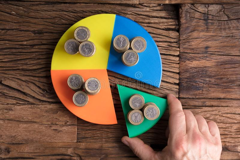 Businessperson Taking Piece With Money From Pie Chart stock photography