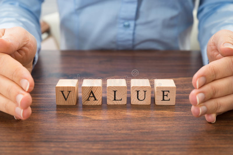Businessperson with value word on blocks. Businessperson Hand Protecting Value Word On Wood Blocks royalty free stock photography