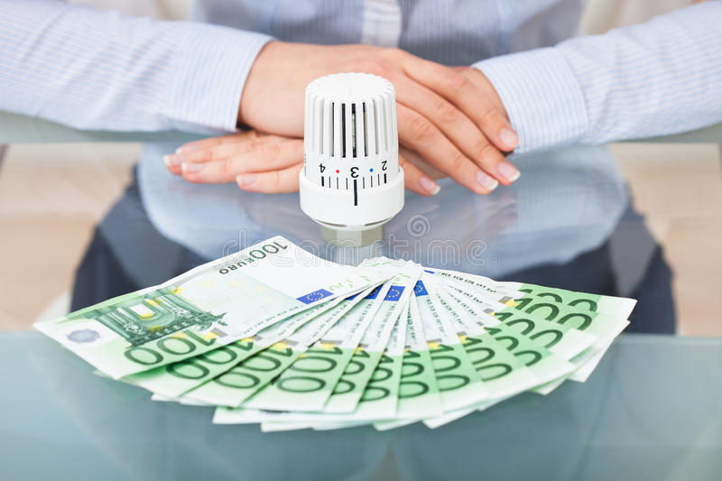 Businessperson with valve and money. Close-up Of Businessperson With Thermostatic Valve And Banknotes stock images