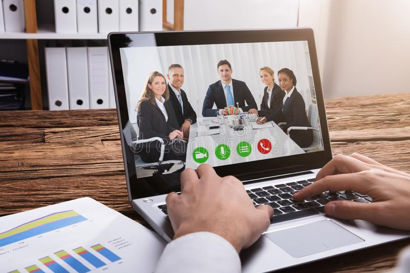 Businessperson Video Conferencing With Colleagues On Laptop. Close-up Of A Businessperson`s Hand Video Conferencing With Colleagues On Laptop royalty free stock photo