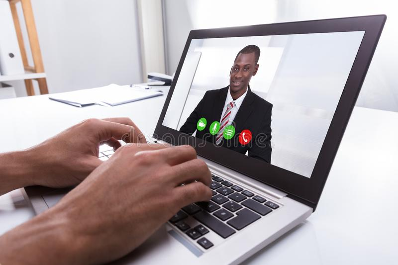 Businessperson Video Conferencing With Male Colleague On Laptop royalty free stock image